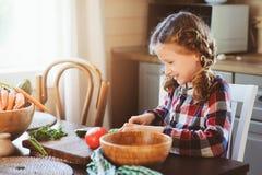 儿童女孩帮助妈妈烹调和切开沙拉的新鲜蔬菜与刀子 免版税库存图片