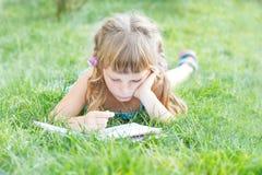 儿童女孩户外阅读书在自然本底 库存图片