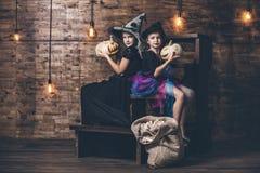 儿童女孩打扮巫婆用南瓜和款待在 免版税图库摄影