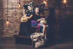 儿童女孩打扮巫婆用南瓜和款待在 免版税库存照片