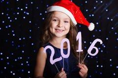 儿童女孩拿着2016个纸图,新年 免版税库存照片