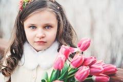 儿童女孩春天接近的画象有郁金香花束的在步行 免版税库存图片