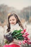 儿童女孩春天画象有郁金香花束的在步行 免版税库存照片