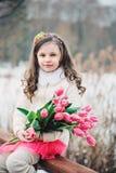 儿童女孩春天画象有郁金香花束的在步行 库存照片