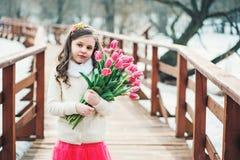 儿童女孩春天画象有郁金香花束的在步行 库存图片