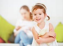 儿童女孩是愉快的诞生新的小兄弟或姐妹 免版税库存图片