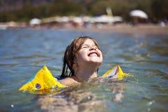 儿童女孩游泳画象在水中 免版税库存照片