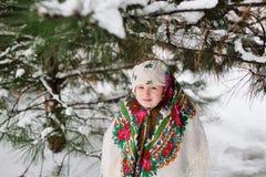 儿童女孩的画象一个头巾的在雪和森林背景的乌尔斯样式  库存照片