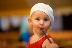 儿童女孩的画象一件白色帽子和红色礼服的,喝从秸杆的三岁的孩子 免版税库存照片