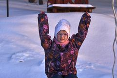 儿童女孩的画象玻璃的在一个晴朗的冬天晚上 女孩享受晚上步行 女孩` s面孔由镭点燃 免版税库存图片
