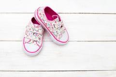 儿童女孩的` s鞋子在木背景的小花的 Fl 免版税库存图片