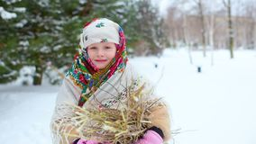 儿童女孩皮大衣的和在俄国样式的一条围巾的与一束草丛 股票录像