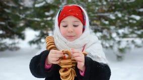 儿童女孩皮大衣的和在俄国样式的一条红色围巾的吃在雪和森林背景的百吉卷  股票录像