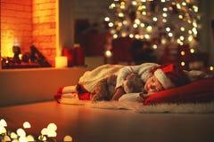 儿童女孩睡着了在圣诞前夕的近的树 免版税图库摄影