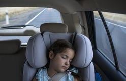 儿童女孩睡着在汽车的儿童安全位子 库存图片