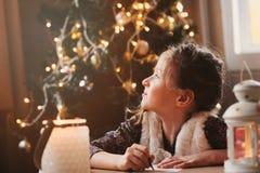 儿童女孩给圣诞老人的文字信件在家 8岁在家做礼品单的女孩圣诞节或新年 免版税库存照片