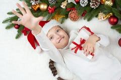 儿童女孩获得乐趣激动圣诞节装饰、面孔表示和愉快的,穿戴在圣诞老人帽子,在白色毛皮backgr说谎 库存图片