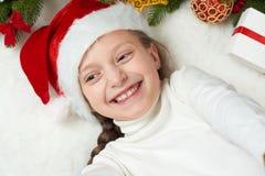 儿童女孩获得乐趣激动圣诞节装饰、面孔表示和愉快的,穿戴在圣诞老人帽子,在白色毛皮backgr说谎 图库摄影