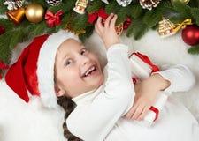 儿童女孩获得乐趣激动圣诞节装饰、面孔表示和愉快的,穿戴在圣诞老人帽子,在白色毛皮backgr说谎 免版税图库摄影