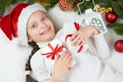 儿童女孩获得乐趣激动圣诞节装饰、面孔表示和愉快的,穿戴在圣诞老人帽子,在白色毛皮backgr说谎 库存照片