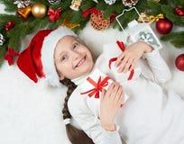 儿童女孩获得乐趣激动圣诞节装饰、面孔表示和愉快的,穿戴在圣诞老人帽子,在白色毛皮backgr说谎 免版税库存照片