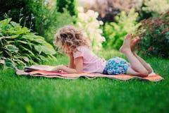 儿童女孩阅读书在庭院里,学会暑假 库存图片