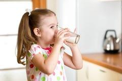 儿童女孩饮用的酸奶或牛奶在厨房里 库存照片