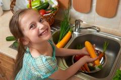 儿童女孩洗涤的菜和新鲜水果在内部的厨房,健康食物概念里 免版税库存照片