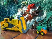 儿童婴孩在操场戏弄拖拉机和卡车在木地板上 免版税库存照片