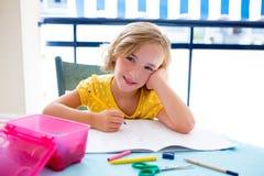 儿童学员孩子女孩愉快微笑与家庭作业 免版税库存照片