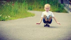 儿童孩子坐获得的滑板室外的乐趣 库存图片