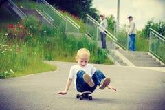 儿童孩子坐获得的滑板室外的乐趣 免版税图库摄影