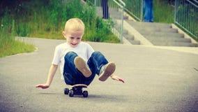儿童孩子坐获得的滑板室外的乐趣 免版税库存图片