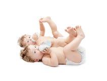 儿童孪生说谎吮牛奶瓶 图库摄影