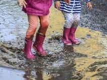 儿童室外跃迁到在起动的水坑里在雨以后 免版税库存图片