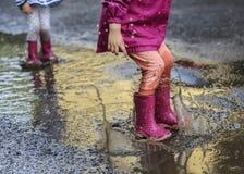 儿童室外跃迁到在起动的水坑里在雨以后 免版税图库摄影