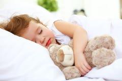 儿童小女孩在与玩具熊的床上睡觉 库存照片