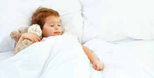儿童小女孩在与玩具熊的床上睡觉 免版税图库摄影