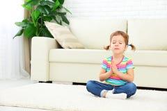 儿童小女孩在莲花坐思考并且实践瑜伽 图库摄影
