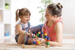 儿童小孩女孩和妈妈在家使用与教育玩具在托儿所 库存图片