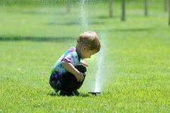 儿童展开的喷水隆头 库存图片
