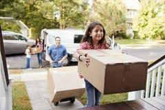 儿童帮助卸载Boxes From范On移动在天的Family 免版税库存照片