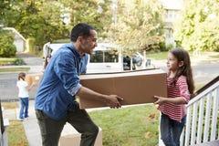 儿童帮助卸载Boxes From范On移动在天的Family 库存图片