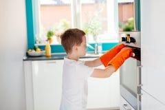 儿童开头烤箱在厨房里 免版税库存图片