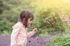 儿童愉快的小女孩嗅到的花在庭院里 免版税库存照片