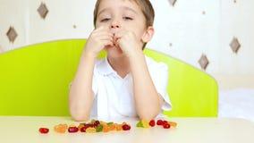 儿童愉快的纵向 一个小男孩坐在桌上并且采取明亮的果子糖果,橘子果酱 子项吃 影视素材
