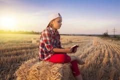儿童户外阅读书或圣经 读圣经的逗人喜爱的小女孩 免版税库存照片