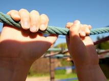 儿童手在一个室外操场拿着塑料上升的绳索 库存照片