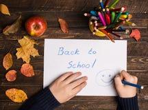 儿童手,蜡笔,苹果和回到在木的学校标志 免版税库存照片