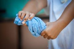 儿童手紧压湿蓝色毛巾 免版税库存图片